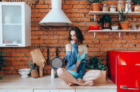 Sexy girl in underwear and jean jacket sitting on table in the kitchen. Healthy eating, diet, lifestyle concept Banco de Imagens