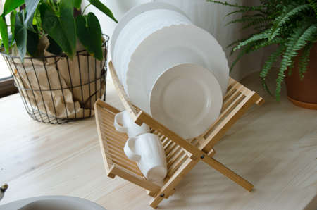 Clean dishes drying on wooden dish rack