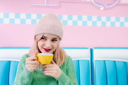 Attractive happy girl in cafe. Pretty girl dressed in a sweater drinking tea in cafe. Pink and blue background