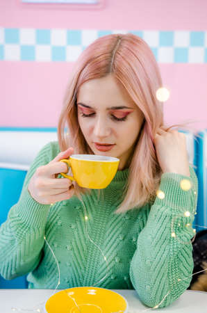Pretty girl drinking tea in cafe. Pink and blue background