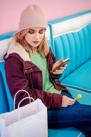 Hipster girl sitting in cafe with shopping bags. Pretty young woman using phone sitting in cafe. Online shopping concept