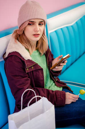 Hipster girl sitting in cafe with shopping bags. Pretty young woman using phone sitting in cafe after the shopping