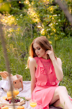 Pretty woman in pink dress in a picnic. Picnic setting on the grass with basket, bread, orange juice, cheese and fruit