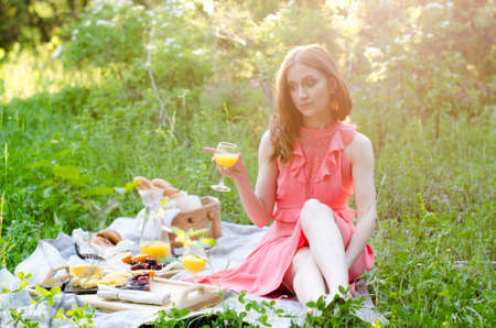 The red haired woman in park outside. Picnic setting on the grass with basket, bread, cheese, orange juice and fruit Banco de Imagens