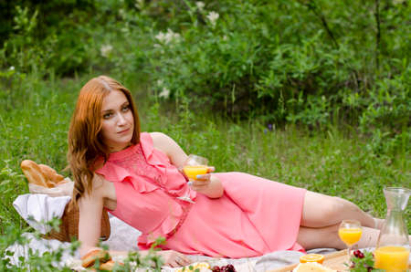 The red haired woman in park outside. Picnic setting on the grass with basket, bread, cheese and fruit