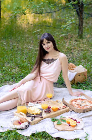 Beautiful young woman having picnic on sunny spring day. Picnic setting on the grass with basket, bread, cheese and fruit Banco de Imagens