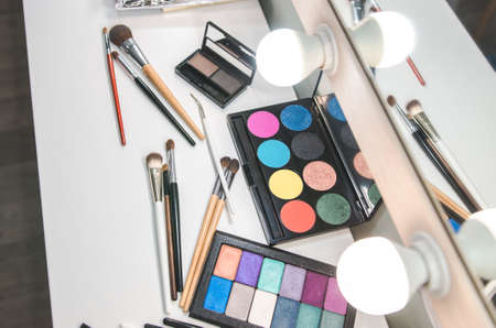 Different makeup products on table near mirror. Makeup studio