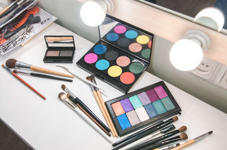 Professional cosmetic products for makeup on table near mirror