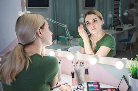 Woman correcting eyebrows form. Young pretty woman making make-up near mirror in studio
