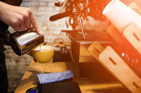 El proceso de hacer café en la cafetería. Cerca de barista preparando café con leche fresco Foto de archivo