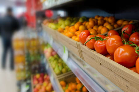 Fruits and vegetables on shelves in supermarket. Unrecognizable customer as background
