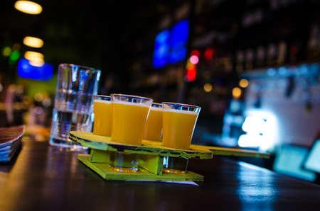 Set mit gelben Shots in einer Reihe, vier Portionen auf einem Holzständer