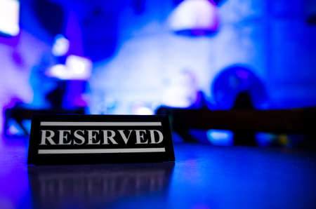 Black plastic signboard place on the wooden dining table. Restaurant background Foto de archivo