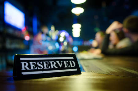Reserved sign standing on wooden table in bar. Pub interior