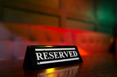 Reserved sign standing on on wooden table in bar Foto de archivo