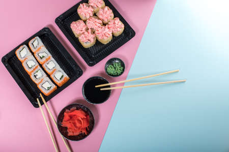 Sushi rolls set with red mayonnaise sauce and Philadelphia in black box. Food delivery. Pink and blue background