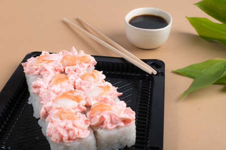 Sushi rolls topped with pink cream cheese and shrimp. Sushi rolls set in black plastic containers with soy sauce and chopsticks