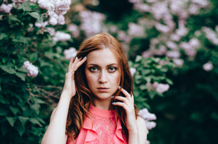 Attractive young woman with perfect red long hairs in a garden with lilacs Imagens