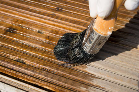 Close up of using a brush to apply stain to wood decking