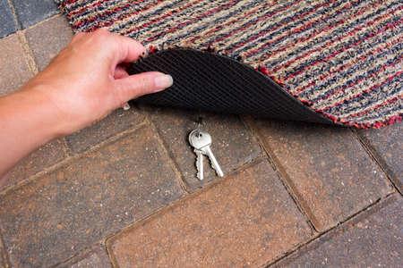 Person lifting a door mat to reveal a hidden key Banco de Imagens