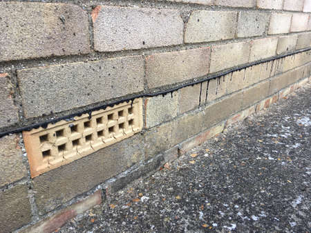 Brickwork of a house showing a line of damp proofing along with an air brick Stok Fotoğraf