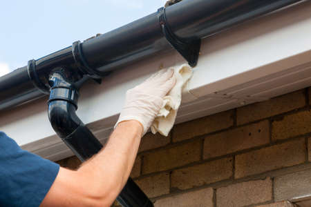 Property Maintenance - Man cleaning eaves or gutters with a cloth Stock fotó - 107433720