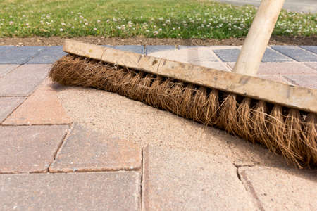 Brushing in kiln dried sand to newly laid block paving with a broom Banque d'images