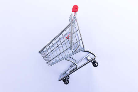 Side view of a mini wire shopping trolley on a white background