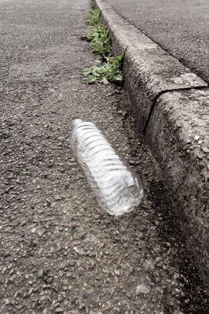 Empty plastic drinks bottle discarded in the gutter of a street