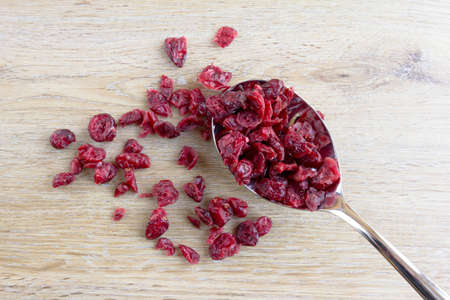 Dried cranberries on a spoon and light wood background