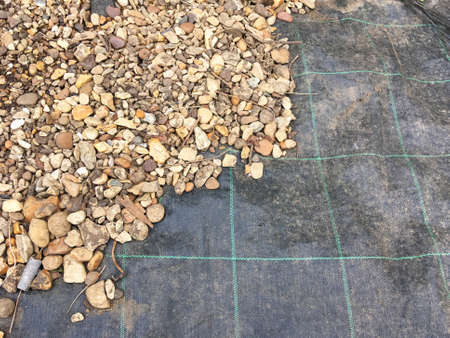 Weed control fabric-  half covered with stones and pebbles.