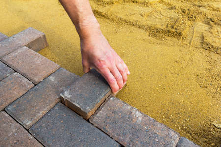 Person laying block paving on to sharp sand