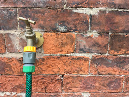 Hose pipe connected to a tap in a red brick wall - copy space provided