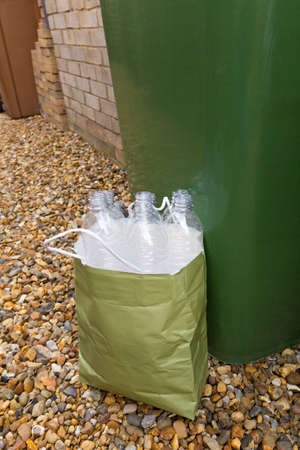 Empty plastic drinks bottles in a paper bag next to a recycling bin
