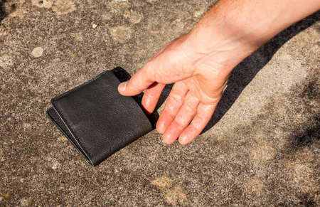 Man picking up a discarded wallet