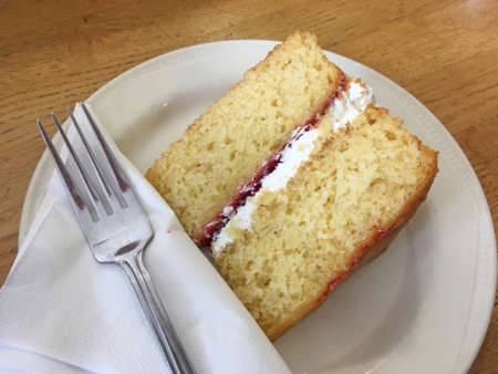 A slice of Victoria Sponge with napkin and fork.