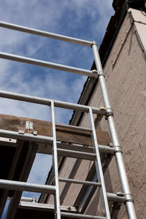 Scaffold tower and ladder adjoining the side of a property