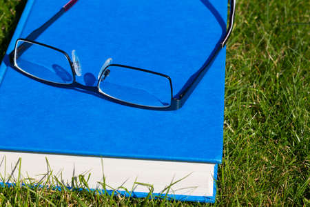 Close up of a hard backed book and reading glasses on a grass background