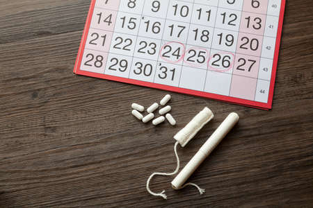 Menstruation Concept - Monthly calendar along with pain killers and tampons