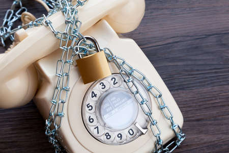 Vintage telephone with a padlock and chain