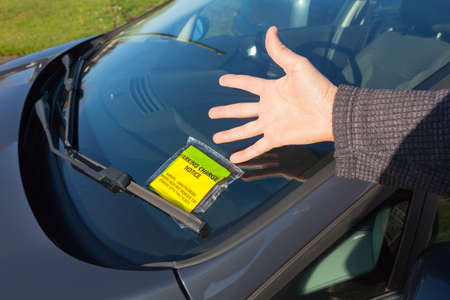 Frustrated motorist with a parking notice attached to the windscreen of a car