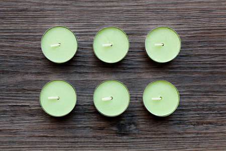 Six green tealights against a dark brown background