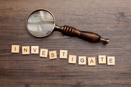 Old fashioned magnifying glass with the word - Investigate