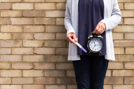 Fertility and biological clock conept - middle aged woman holding a clock and negative pregnancy test