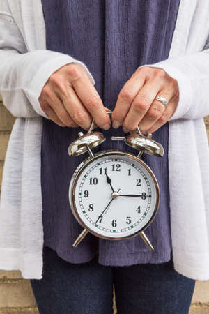 Close up of a clock being held against a womans stomach - biological clock concept