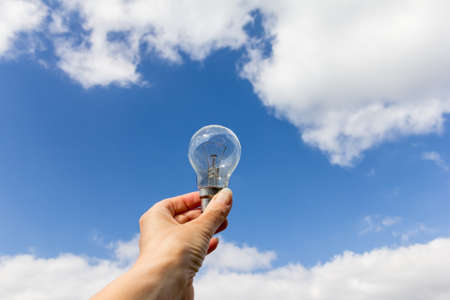 Person holding an old style filament light bulb against a blue sky with white cloud background Stock Photo