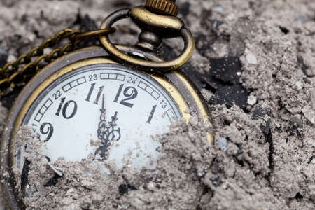 Old fashioned watch amongst ashes