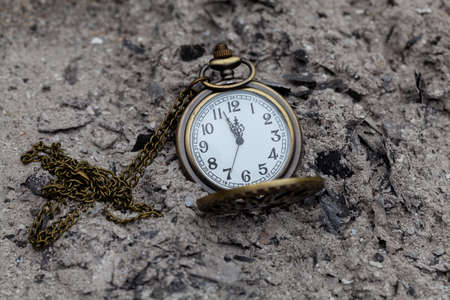 Pocket watch with chain on a pile of ashes