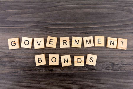 The word Government Bonds on a dark wood background Фото со стока