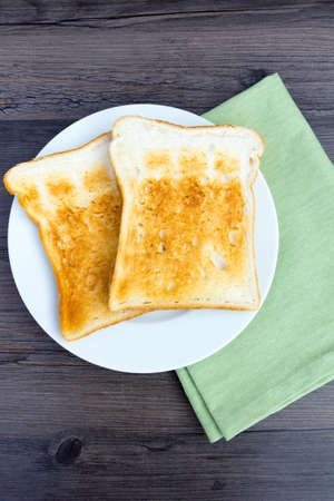 Plain white toast without butter on a plate with a napkin Фото со стока
